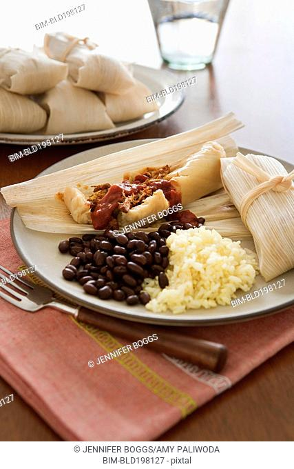 Tamales, beans and rice on plate