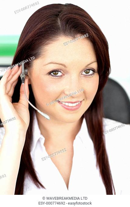 Attractive young businesswoman wearing earpiece in a customer service sitting at her desk