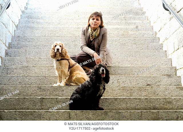 Elegant woman sitting on stairs with her two cocker spaniel dogs