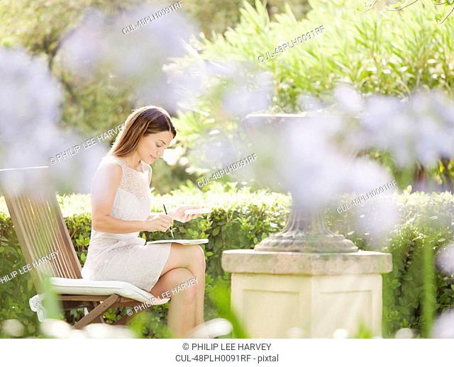 Woman using tablet computer in garden