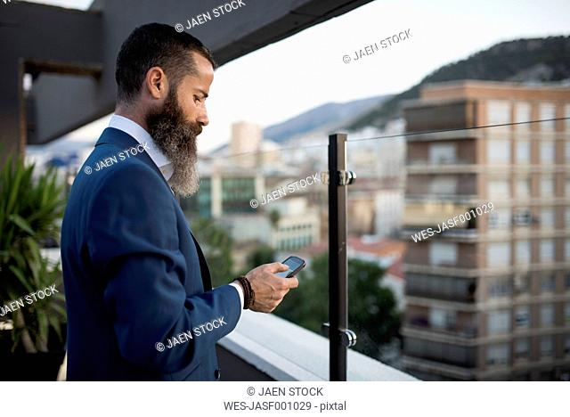 Bearded businessman standing on roof terrace looking at cell phone