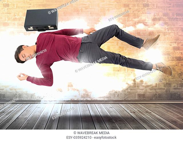 Businessman with briefcase floating magically over cloudy wall with illuminated light bursts