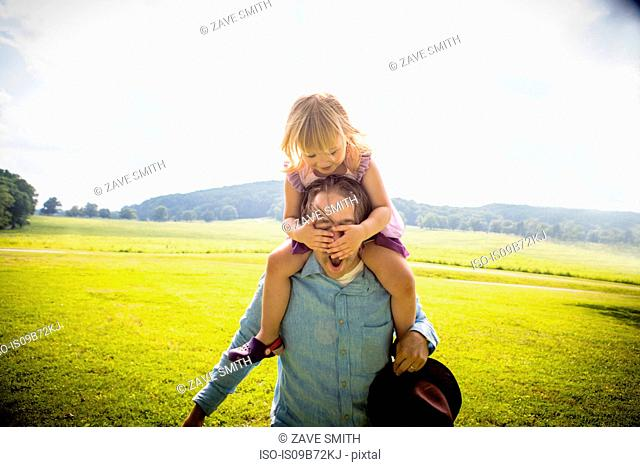 Girl getting piggy back from father in rural field, covering his eyes