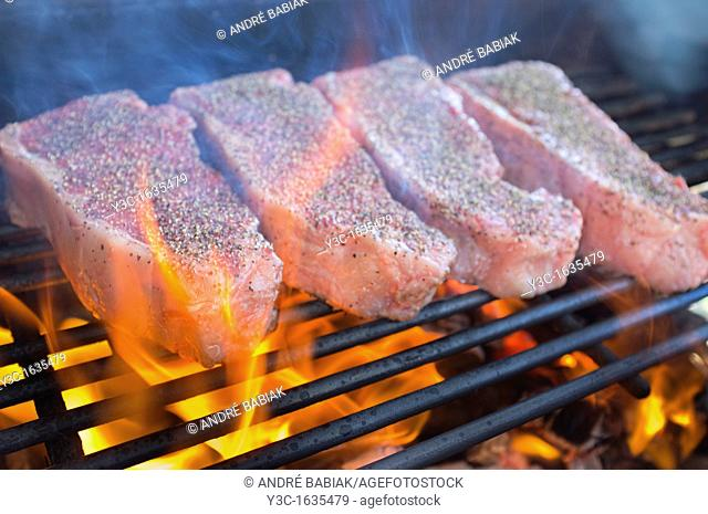 Seasoned beef strip loin steaks grilled over hot fire barbecue pit