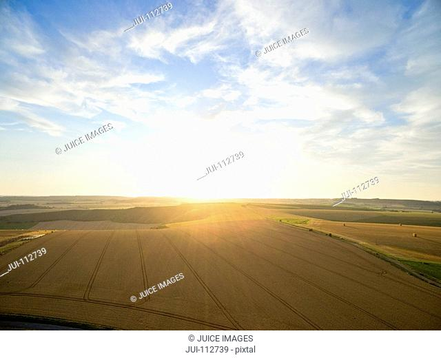 Aerial landscape view of sunset over golden barley fields in rural countryside