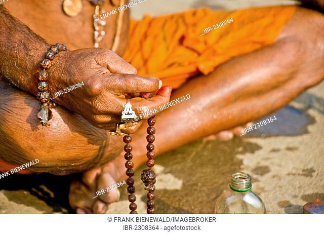 Sadhu, holy man, doing his washing and praying ceremony in the morning at the holy Narmada river, Omkareshwar, India, Asia