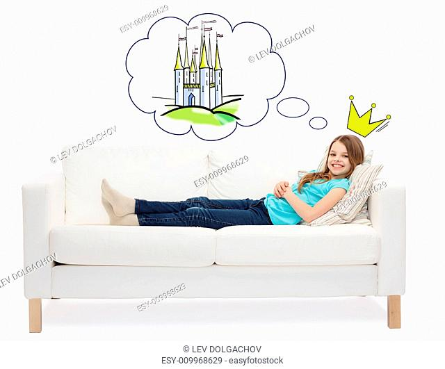 home, leisure, people and happiness concept - smiling little girl lying on sofa dreaming about fairy castle and princess crown