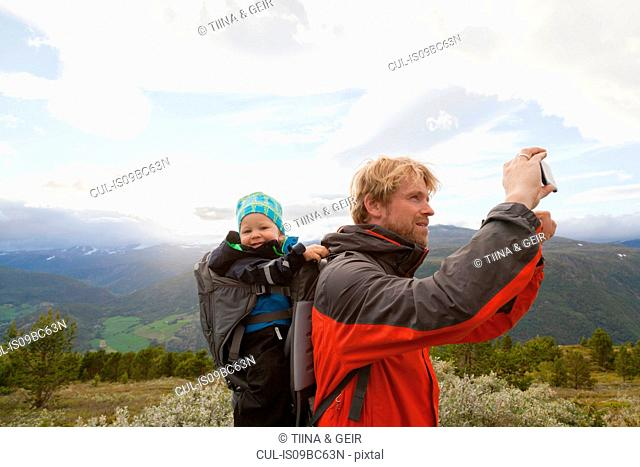 Male hiker with son photographing mountain landscape, Jotunheimen National Park, Lom, Oppland, Norway