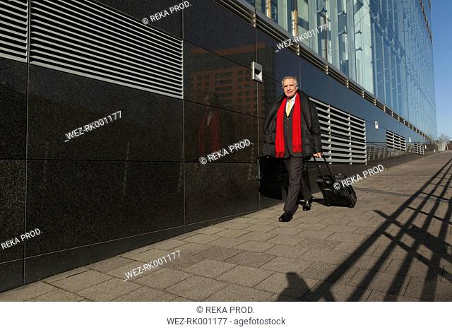 Senior businessman with rolling suitcase on the move