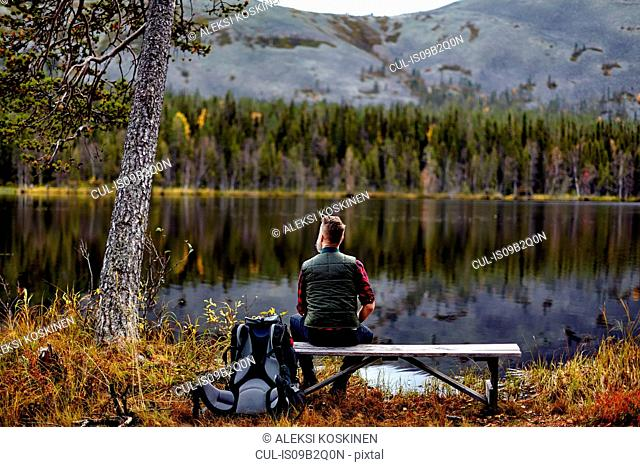 Hiker resting on bench, looking out at lake, Kesankijarvi, Lapland, Finland