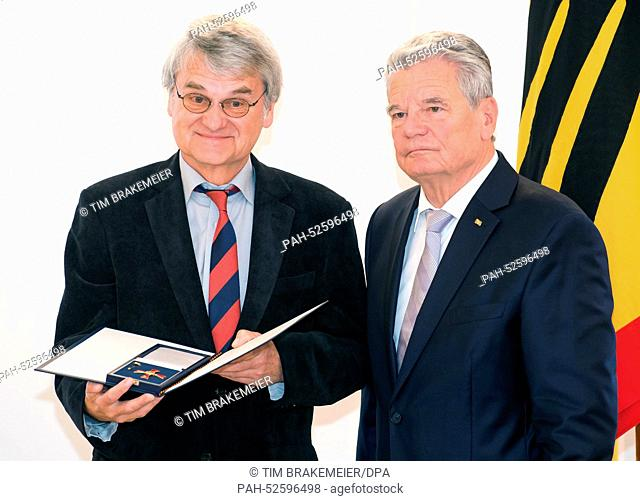 German President Joachim Gauck (R) awards the order of merit on the occasion of German Unity Day to cabaret artist Bernd-Lutz Lange (L) from Leipzig in Berlin