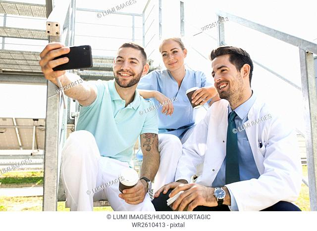 Group of doctors taking a selfie outdoors