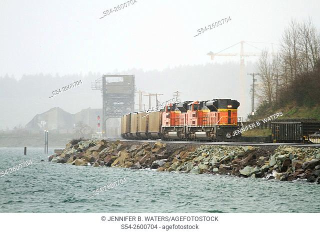 A BNSF train in a rainstorm at Chambers Bay near Sunnyside Beach Park, Tacoma, Washington, USA