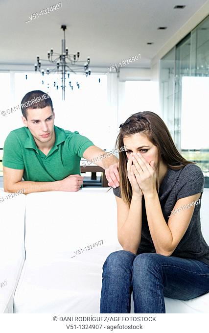 Sad woman in sofa and boyfriend trying to support her