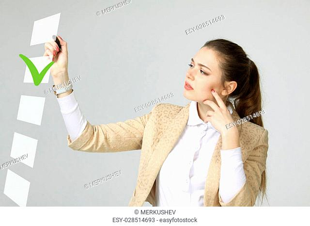 Young business woman checking on checklist box. Gray background. Concept on the topic of elections
