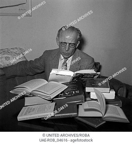 Der deutsche Schriftsteller und Journalist Albin Stuebs über seinen Büchern, Deutschland 1950er Jahre. German author and journalist Albin Stuebs with his books