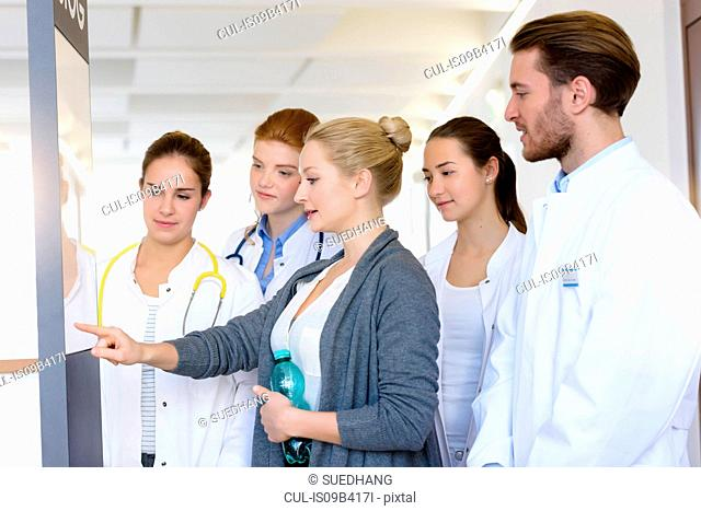 Woman with male and female doctors pointing at chart in hospital