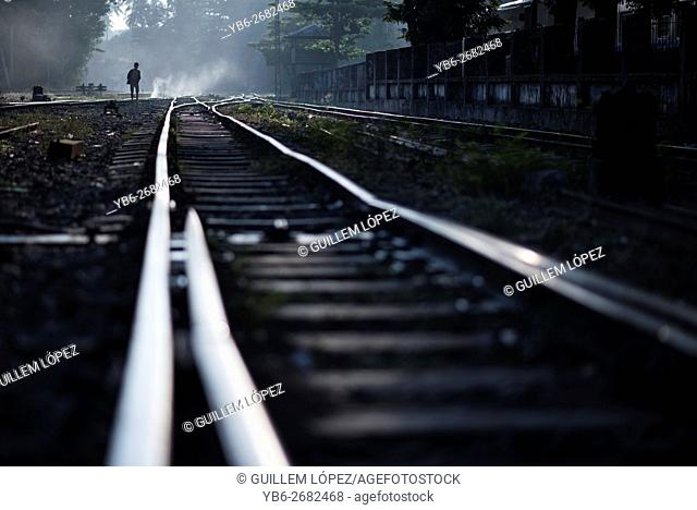 A man walks on the Rail tracks of the Yangon Central Train Station, Myanmar