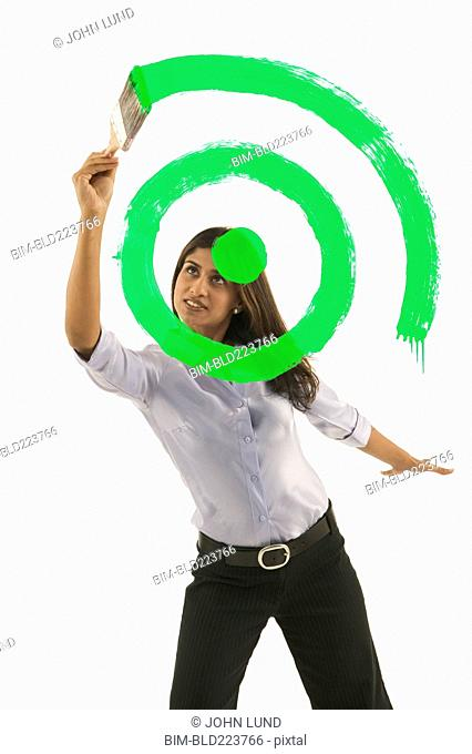 Businesswoman painting green target on glass wall