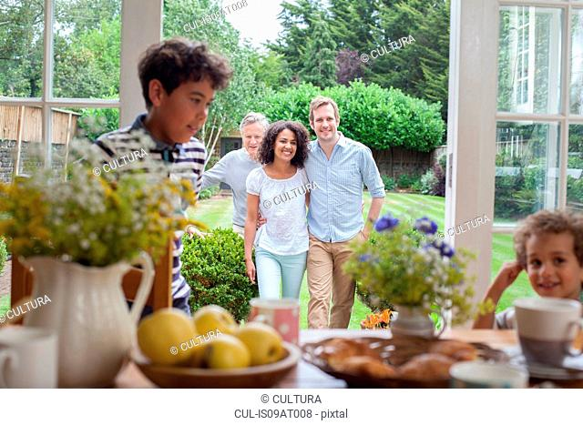 Family coming in for breakfast after walk in garden