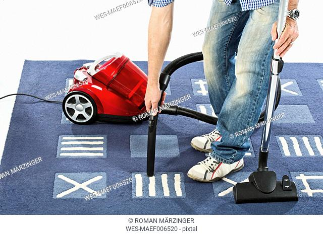 Mature man cleaning carpet with vaccuum cleaner