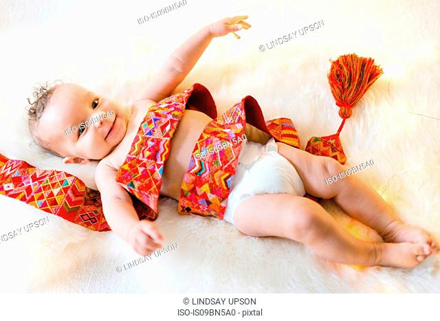 Baby boy wrapped in colourful textile lying on furry rug