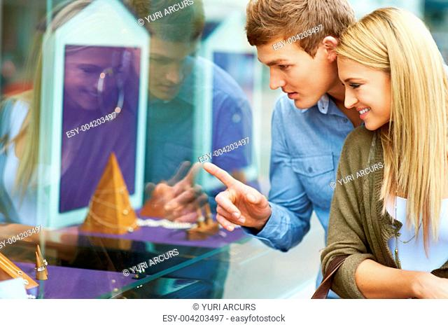 Young couple looking at a jewellery display through a shop window