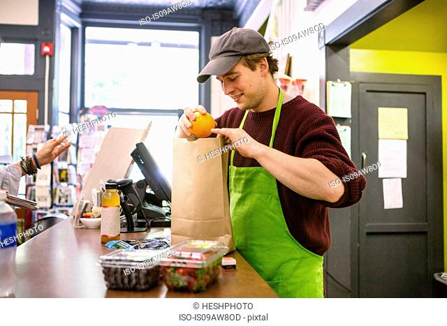 Employee in general store serving customer at counter