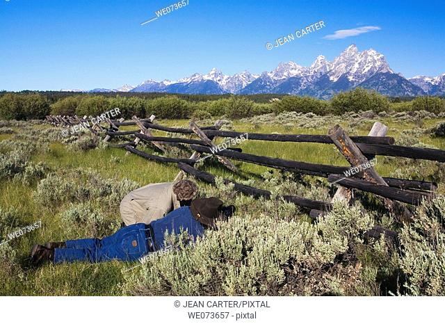 John & Judith Uno work together to photograph the Grand Teton Mountains framed through opening in a Buck and Rail fence, Grand Teton National Park, Wyoming, USA