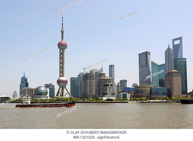 Skyline of the Pudong financial district, with TV Tower, Jin Mao Tower and World Finance Building behind the Huangpu River and freighters, Shanghai, China, Asia