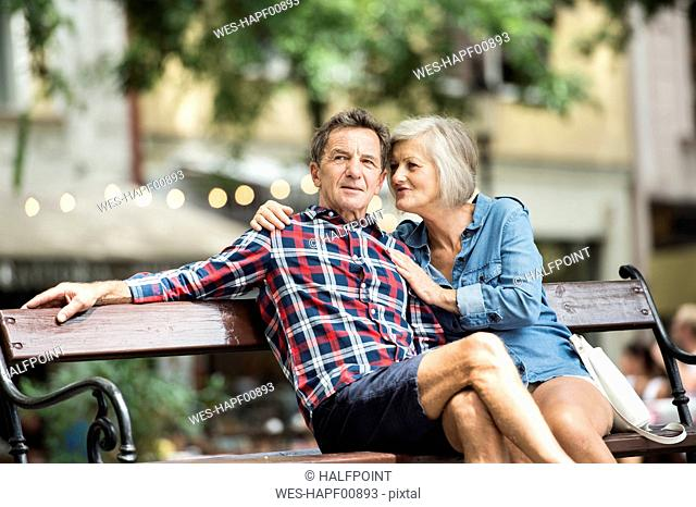 Senior couple sitting on bench watching something