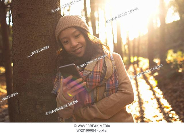 Beautiful woman in warm clothing using mobile phone