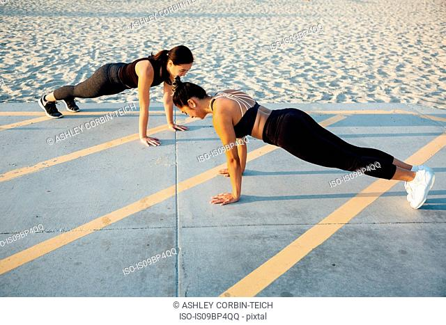 Friends doing exercises by beach