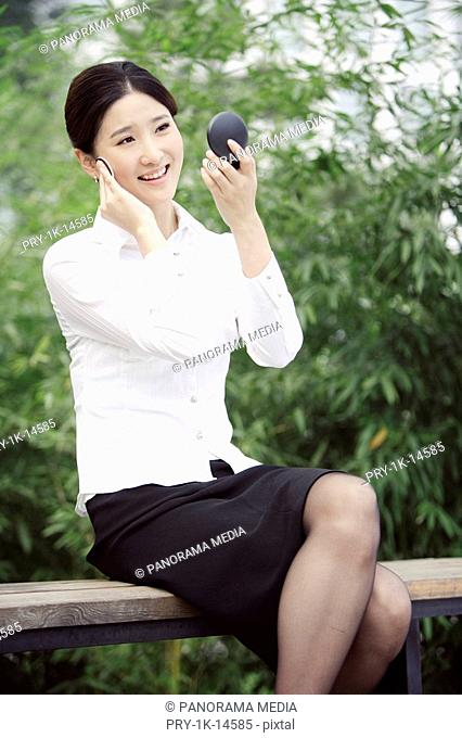 Businesswoman applying make-up, smiling