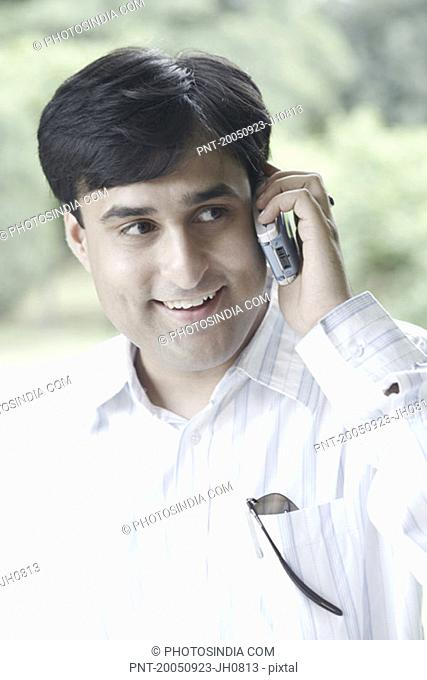 Young man talking on a mobile phone smiling