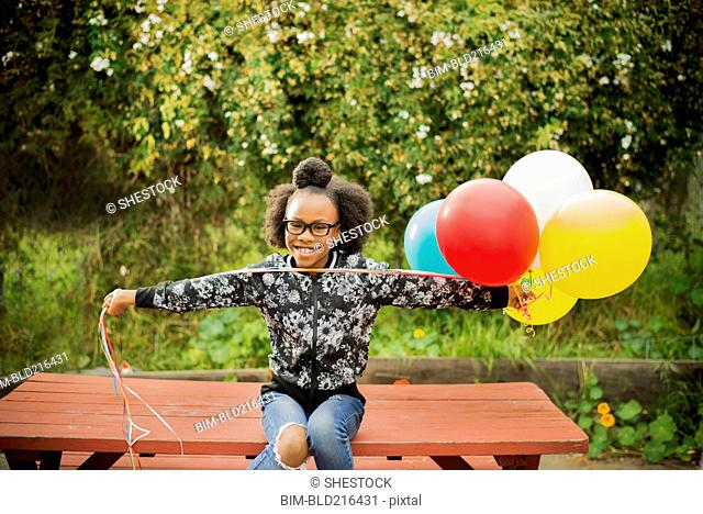 Black girl holding bunch of balloons on picnic table