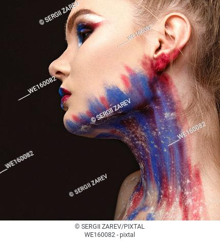 Studio Portrait of a young model girl with stylish makeup in a dark blue tones