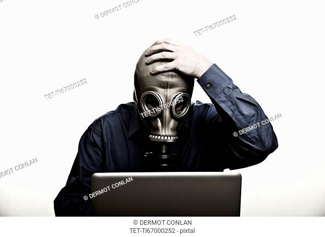 Studio shot of man in front of laptop wearing gas mask