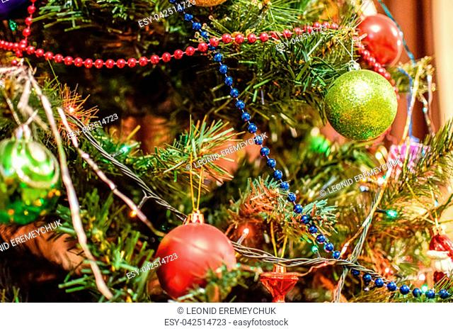 Tinsel and toys, balls and other decorations on the Christmas Christmas tree standing in the open air. Decorations New Year tree