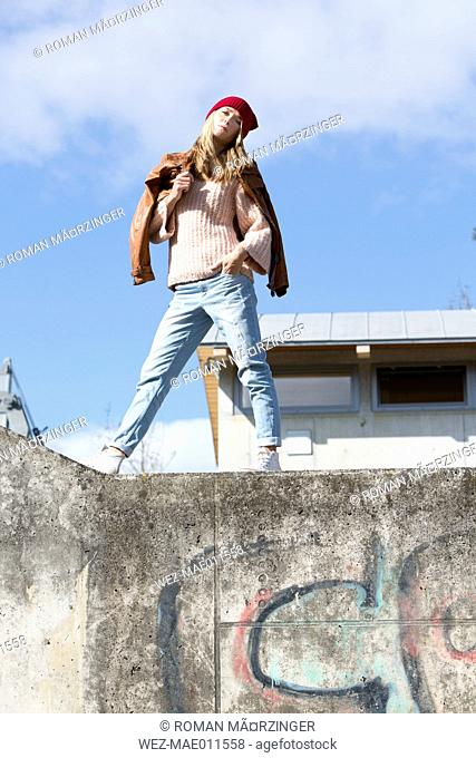 Young blond girl on wall