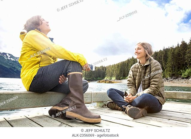 Two young woman sitting on a wooden dock at the water's edge laughing and talking; Alaska, United States of America