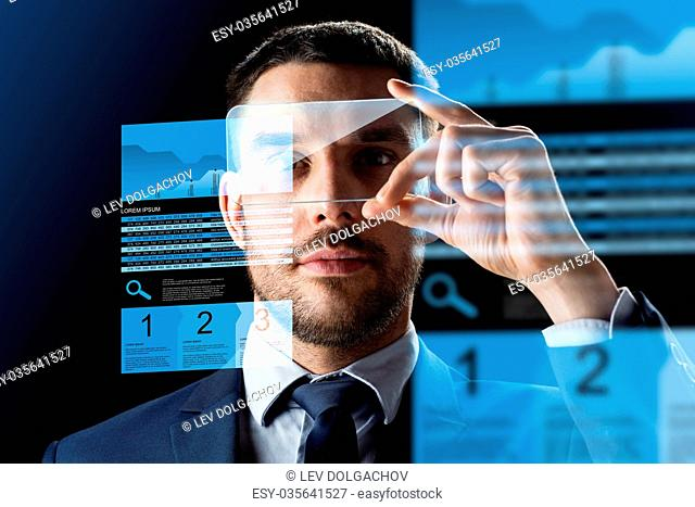 business, augmented reality and modern technology concept - businessman working with transparent smartphone and virtual exchange charts projections over black...
