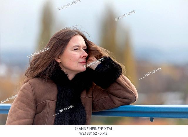 Woman waiting on bridge looking into distance, leaning head on hand,bridge,Bonn,Germany