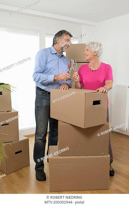 Senior couple moving into new home celebrating with champagne, Bavaria, Germany
