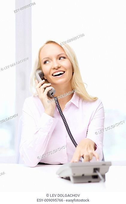 education, business, communication and technology concept - smiling businesswoman calling on phone in office