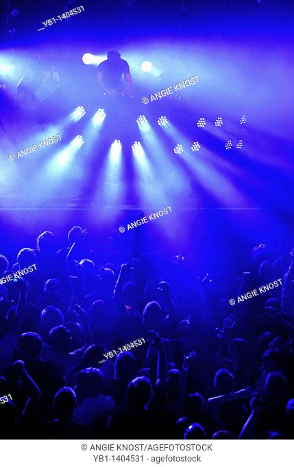 DJ and crowd at dance party, disco or rave