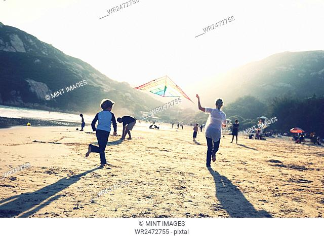 Children flying kites on a sandy beach