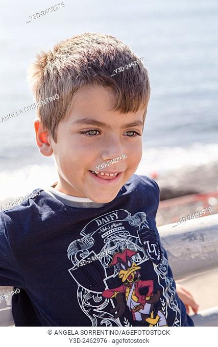 Cute young boy portait outdoors in a sunny sea pormenade