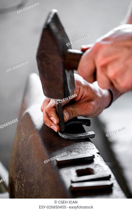 Blacksmith forges a horseshoe. Hammering glowing steel