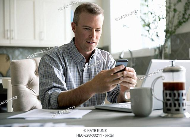 Man texting with cell phone at laptop in kitchen